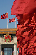 Red flags wave in the wind over China's parliament building, The Great Hall of the People, which bears the communist party emblem.
