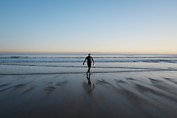 © Licensed to London News Pictures. 12/03/2014<br /> <br /> Saltburn, Cleveland, United Kingdom<br /> <br /> A surfer walks out into the sea as he goes for an early morning surf as the first light of dawn breaks over Saltburn in Cleveland.<br /> <br /> Photo credit : Ian Forsyth/LNP