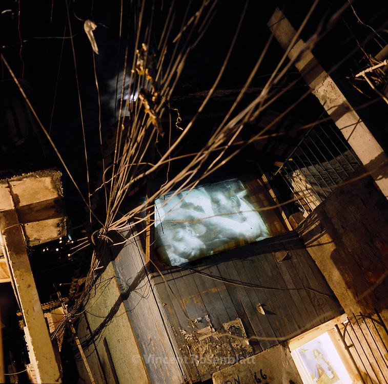 Slide show of the cultural association Olhares do Morro on the walls of the houses in Santa Marta, favela in the south zone of Rio de Janeiro.. ||.Projeção das fotos da ONG  Olhares do Morro nos muros da favela Santa Marta, zona sul do Rio de Janeiro.