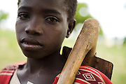 Boy holding a plow on his shoulder as he heads to the field to work near the village of Dungu, Ghana on Friday June 8, 2007..