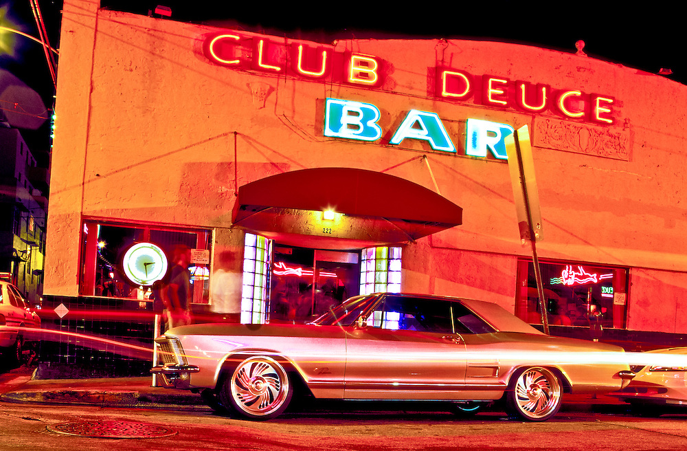 A 1965 Buick Riviera  in front of Mac's Club Deuce Bar, a famous Miami Beach watering hole and dive bar where celebrities and supermodels rub shoulders with bag ladies and bums. The building is a mixture of Florida Mediterranean Revival architecture with later, Art Deco touches, notably the neon-lit, glass brick, door treatment.