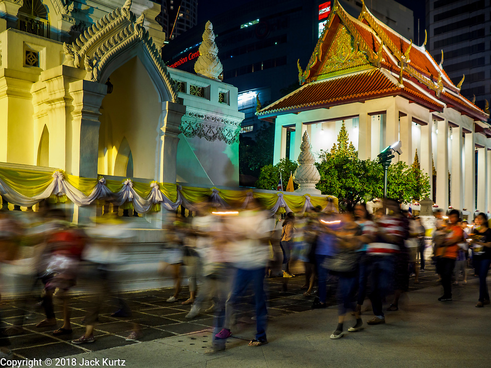 """01 MARCH 2018 - BANGKOK, THAILAND:    People participate in a procession around Wat Pathum Wanaram in central Bangkok. Many people go to temples to perform merit-making activities on Makha Bucha Day, which marks four important events in Buddhism: 1,250 disciples came to see the Buddha without being summoned, all of them were Arhantas, or Enlightened Ones, and all were ordained by the Buddha himself. The Buddha gave those Arhantas the principles of Buddhism. In Thailand, this teaching has been dubbed the """"Heart of Buddhism.""""    PHOTO BY JACK KURTZ"""