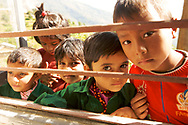 Medical Trek to Nepal with Medical Outreach of America finds children gathering around an open window to watch medical team working.