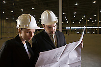 Colleagues study blueprint in empty warehouse