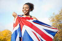 Smiling young woman holding British flag against trees and sky