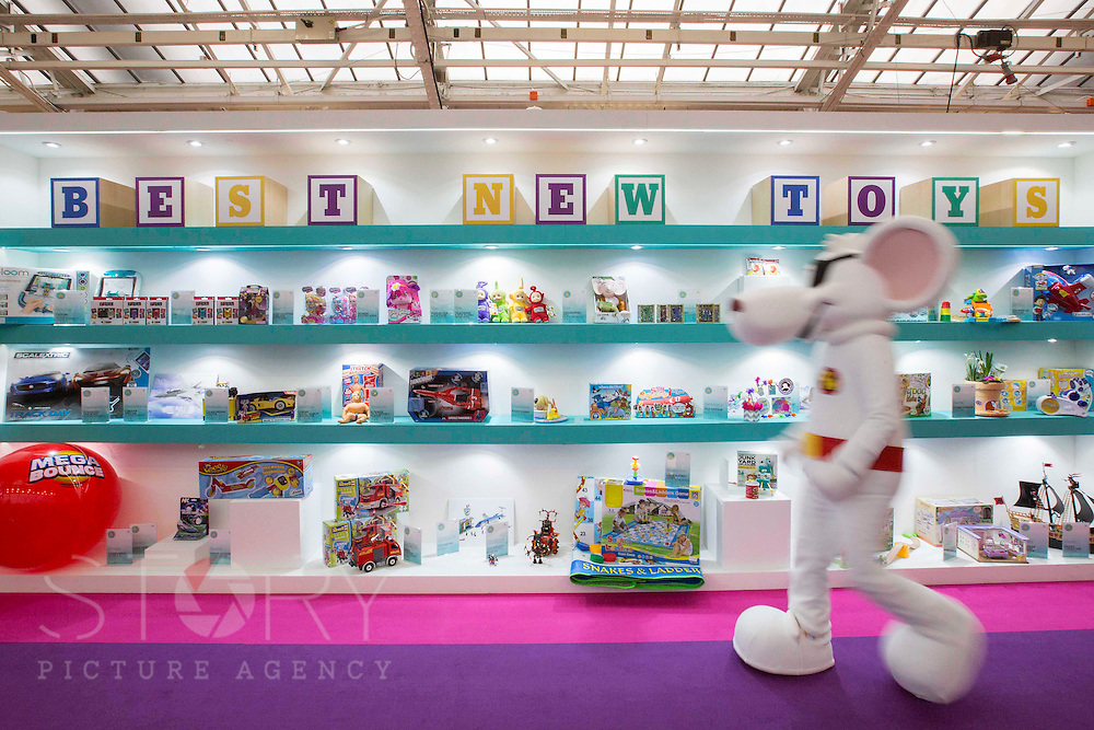 """UNITED KINGDOM, London: 25 January 2016 Danger Mouse walks past a display showing the """"Best New Toys"""" at Olympia in London this morning during The Toy Fair, the UK'S only dedicated game and hobby event with more than 260 toy and gaming brands. The fair runs until tomorrow. Rick Findler / Story Picture Agency"""