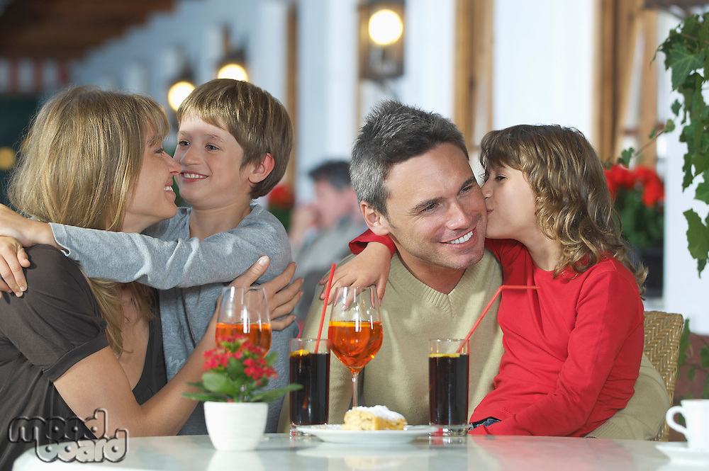Parents and children (7-9) with drinks embracing at restaurant