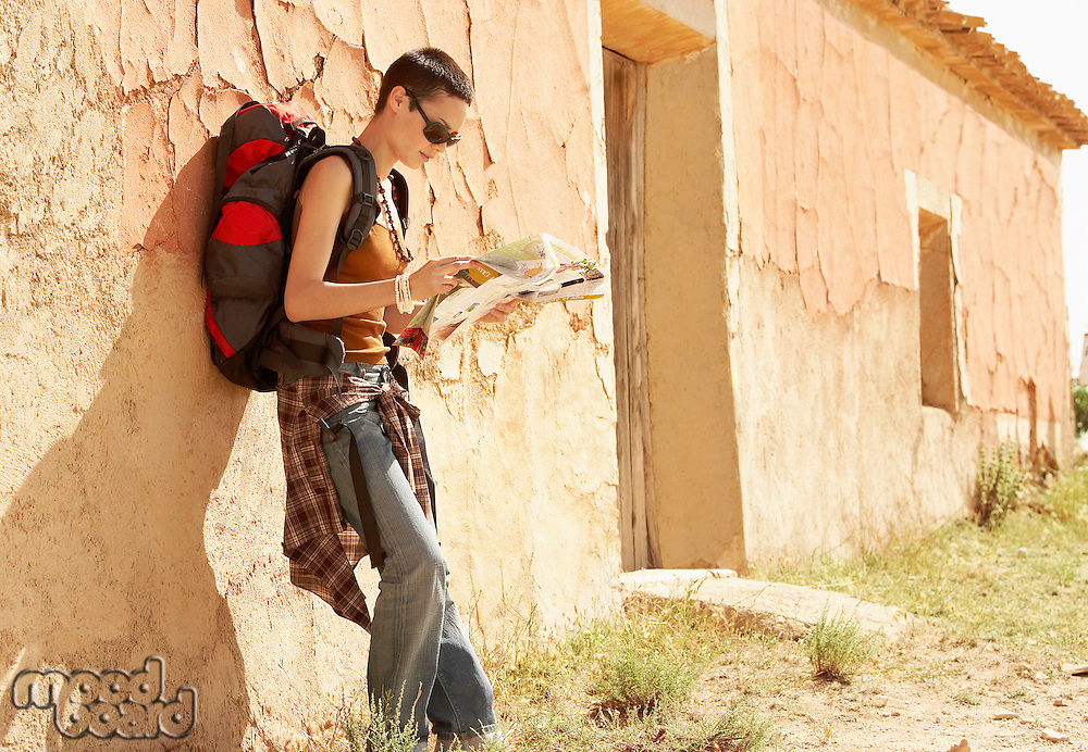 Female hiker reading map by desolate farmhouse