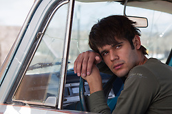young man in sitting in an old truck leaning on the steering wheel