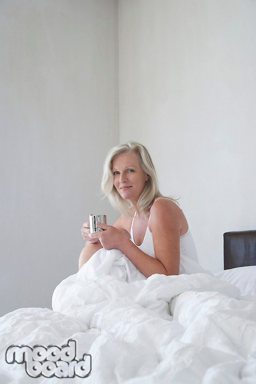 Smiling Mature woman in pyjamas holding cup sitting up in bed side view