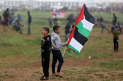 March 30, 2019 - Gaza, Palestine - Palestinian protesters  during clashes with Israeli forces following a demonstration marking the first anniversary of the ''March of Return'' protests, near the border with Israel east of Gaza City on March 30, 2019. - This marks the first anniversary of the often violent weekly border demonstrations in which around 200 Palestinians and an Israeli soldier have been killed, coming just 10 days before a keenly contested general election in Israel. The border protests peaked in May 2018, when Israeli forces shot dead at least 62 Palestinians in a single day in clashes over the transfer of the US embassy to Israel to the disputed city of Jerusalem. (Credit Image: © Majdi Fathi/NurPhoto via ZUMA Press)