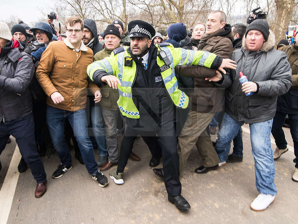 """© Licensed to London News Pictures . 18/03/2018 . London , UK . Police intervene as supporters and those opposed to the speech fight at Speakers Corner . Alt-right groups , including Generation Identity and the Football Lads Alliance , at Speakers' Corner in Hyde Park ahead of Tommy Robinson reading a speech by Generation Identity campaigner Martin Sellner . Along with Brittany Pettibone , Sellner was due to deliver the speech last week but the pair were arrested and detained by police when they arrived in the UK , forcing them to cancel an appearance at a UKIP """" Young Independence """" youth event , which in turn was reportedly cancelled amid security concerns . Photo credit: Joel Goodman/LNP"""
