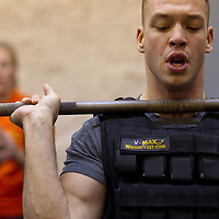 Aaron Bratkovics does a thruster while wearing a weight vest at Progressive Fitness CrossFit.