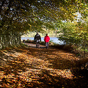 Couple walking at Ogden Water reservoir near Halifax, West Yorkshire, in Autumn.