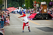 Mickey Metcalf of Coeur d'Alene proudly swings an American flag during the city's Fourth of July Parade at the intersection of Third Street and Sherman Avenue on Sunday afternoon.