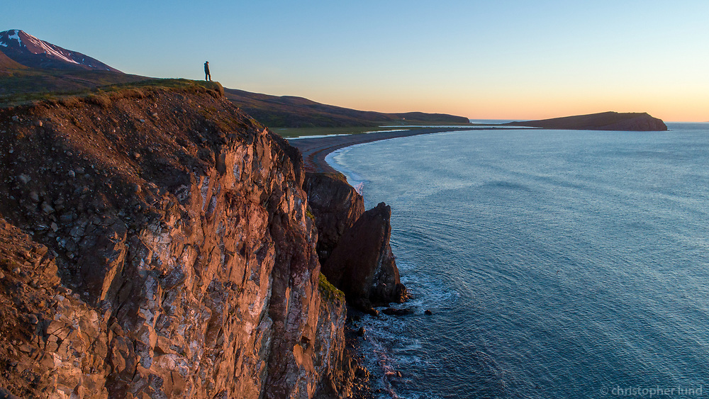 A person looking out to sea from Hofshöfði by Flateyjardalur valley at sunrise. Aerial Drone Shot. North Iceland.