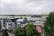 Nederland, Nijmegen, 11-6-2016Uitzicht op Lent,Veur-Lent, onderdeel van de Waalsprong. de bebouwing aan de andere oever is op een eiland komem te liggen als gevolg van de nevengeul. Een binnenvaartschip, containerschip,beladen met containers vaart juist onder de brug, waalbrug, doorFoto: Flip Franssen