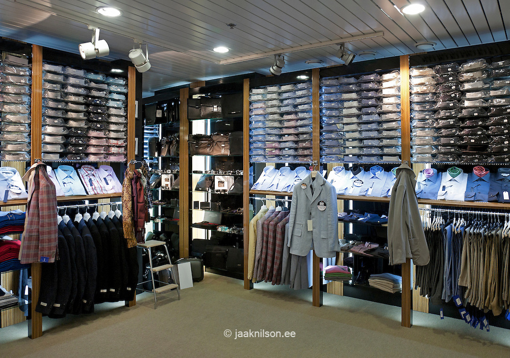 Italian men's fashion shop in Tallinn airport, Estonia. Retail outlet. Display of shirts and suits. Shelves.