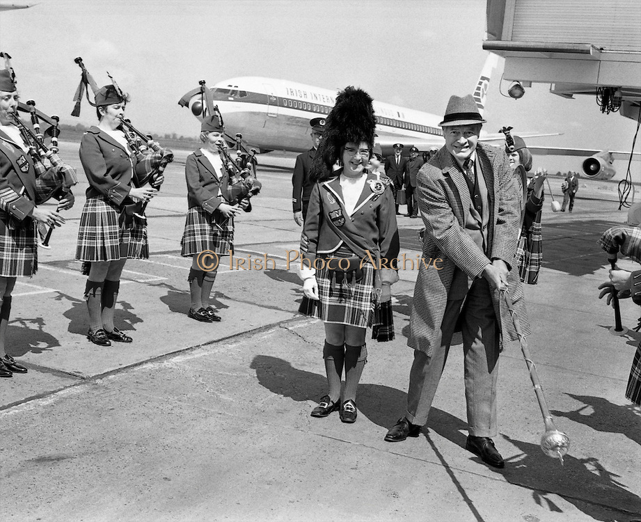 Bob Hope, arriving to attend the premier of his film 'Eight on the Run', amuses the Emerald Girls Pipe Band and their Drum Major, Marie Doran, by finding a new use for her mace.  .01.08.1968