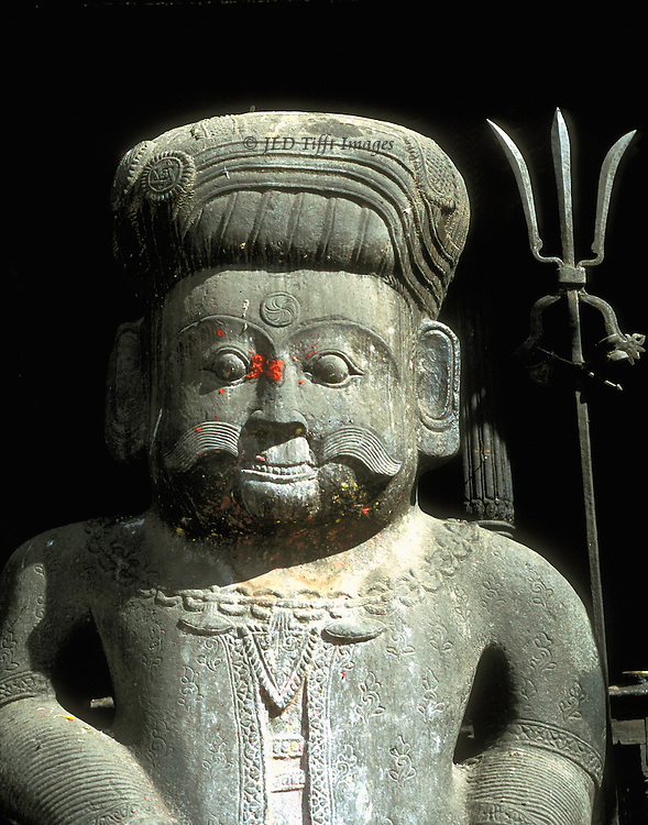 Bhaktapur, World Heritage city, Shiva statue, head & shoulders, trident behind.  The face is daubed with red paint in celebration of Dasain..