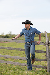 rugged good looking cowboy on a ranch by a spilt rail fence