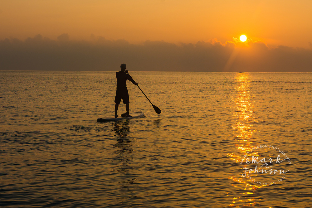 Stand-Up Paddle Boarder watches sun rising in Kailua Bay, Oahu, Hawaii