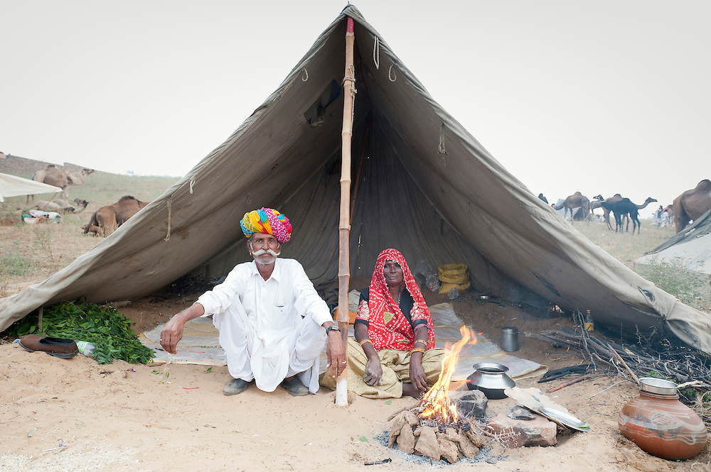 Husband and wife sit outside their tent at Pushkar Fair.