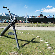 An anchor and PT boat, formerly of the Argentinian Navy, the Ara Towwora, sits on the shore of Ushuaia Harbor as a naval monument.