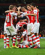 Alexis Sanchez of Arsenal (kneeling) celebrates scoring the opening goal against Besiktas J.K. with team mates during the UEFA Champions League match at the Emirates Stadium, London<br /> Picture by David Horn/Focus Images Ltd +44 7545 970036<br /> 27/08/2014