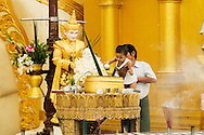 Father and son watering a small Buddha statue