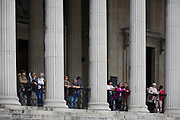 Visitors to the National Gallery admire the view from beneath classical pillars in Trafalgar Square.