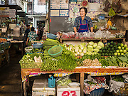 02 SEPTEMBER 2015 - BANGKOK, THAILAND: A vegetable vendor in Bang Chak Market. The Bang Chak Market serves the community around Sois 91-97 on Sukhumvit Road in the Bangkok suburbs. About half of the market has been torn down, vendors in the remaining part of the market said they expect to be evicted by the end of the year. The old market, and many of the small working class shophouses and apartments near the market are being being torn down. People who live in the area said condominiums are being built on the land.         PHOTO BY JACK KURTZ
