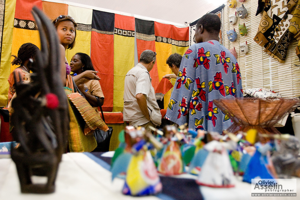 Customers browse items for sale in a stand at the 22nd Salon International de l'Artisanat de Ouagadougou (SIAO) in Ouagadougou, Burkina Faso on Saturday November 1, 2008.