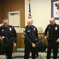 Rajah Bose  |  rbose@tricityherald.com.Ryan Child, 7, salutes his father, Scott Child of the Kennewick Police Department, as his twin brother, Brent, shakes hands with Christian Walters, center, and Matthew Newton after a promotional ceremony Wednesday at Kennewick City Hall. Child was promoted to captain and will command the Criminal Investigation Division. Walters was promoted to sergeant and Newton was promoted to corporal.
