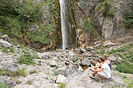 Hikers at a waterfall near Theth, Peaks of the Balkans Trail, Albania © Rudolf Abraham