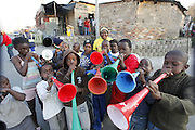 Kids blowing vuvuzelas to celebrate South Africa's second goal against France in the 2010 World cup. Alex township. Johannesburg. South Africa. .Picture by Zute Lightfoot