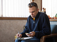 Nick Rhoades looks at his phone as he fills out paper work before an appointment with his psychiatrist at Covenant Clinic Psychiatry in Waterloo, Iowa on Thursday, November 7, 2013.