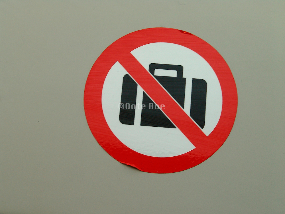 A close up of a no suitcase sign on a window sill in a train.