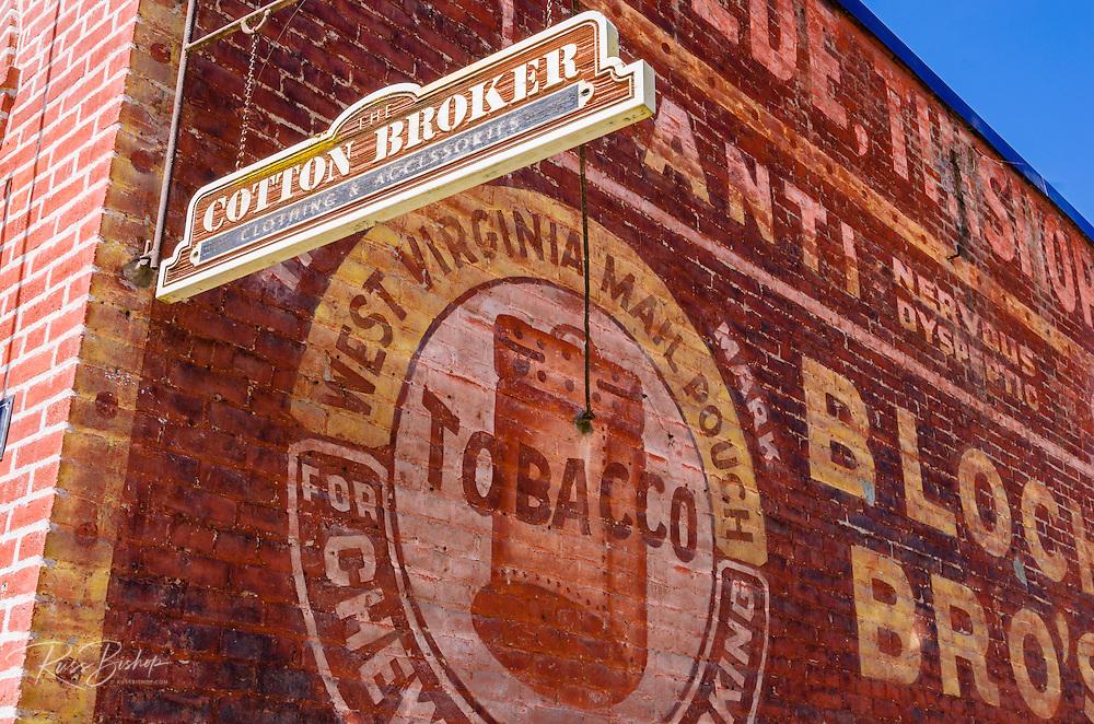 Historic advertisement on brick building and modern shop sign, Jacksonville, Oregon USA