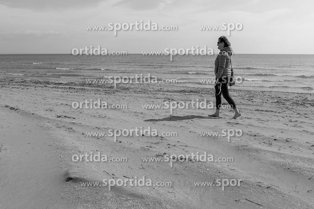 Themenbild - Kaum eine andere Region Italiens ist dermaßen geprägt vom Tourismus wie die Küstenregionen der oberen Adria. In den Hauptbadeorten Grado, Lignano, Bibione, Caorle, Jesolo, Marina die Venezia und auf der Isola Albarella drängen sich jedes Jahr aufs neue wahre Touristenmassen am Strand. Hier im Bild eine Frau wandert am Lido, Strandbad, Sandstrand. Grado, Italien am Samstag, 13. April 2019 // Preseason on the upper Italian Adria. Hardly any other region of Italy is as influenced by tourism as the coastal regions of the upper Adriatic. In the main seaside resorts of Grado, Lignano, Bibione, Caorle, Jesolo, Marina the Venezia and on the Isola Albarella, every year new masses of tourists crowd the beach. Picture shows a woman is walking on Lido, beach, sandy beach. Grado, Italy on Saturday, April 13, 2019. EXPA Pictures © 2019, PhotoCredit: EXPA/ Johann Groder