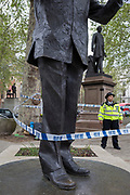 On the 10th consecutive day of protests around London by the climate change campaign Extinction Rebellion, police tape wrapped around the statue of Nelson Mandela and bars entry beneath tree protesters, on 24th April 2019, in Parliament Square, Westminster, London England.