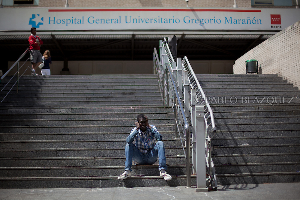 A man sits outside Gregorio Maranon Hospital after a demonstration took part against the Spanish government's latest austerity measures concerning medical care for immigrants, in the center of Madrid, on September 1, 2012. Sign reads 'They are not cuts, they are executions'.