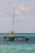 An outrigger canoe with an unfurled sail sits of the coast of Oahu in Hawaii.