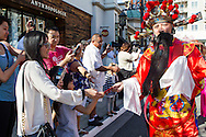 A performer dressed as God of Wealth gives red pockets the people during a parade to celebrate the upcoming Spring Festival or Chinese New Year at The Americana at Brand in Glendale, California, Sunday, February 15, 2015. <br /> (Photo by Ringo Chiu/PHOTOFORMULA.com)