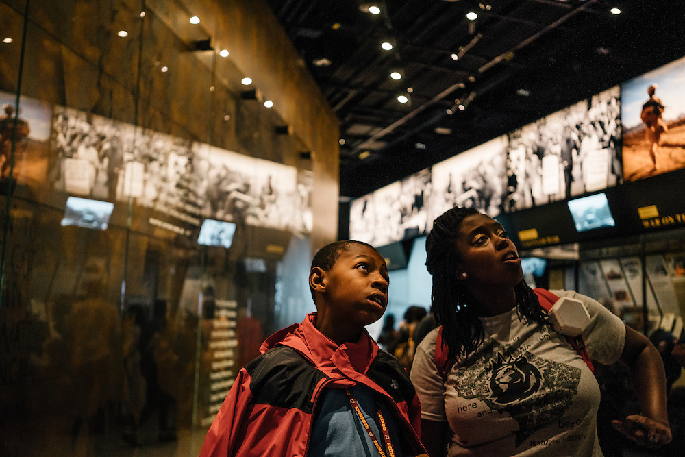 Sixth-graders from Knowledge Is Power Program (KIPP) DC, including Omari Sterling, 11, left, and his teacher Gabrielle Randall, right, look at exhibits inside the Smithsonian National Musuem of African American History and Culture during their visit on Oct 21, 2016. The students spent an hour touring the new Washington, D.C. museum, which is only available to see with reserved tickets during the first year.