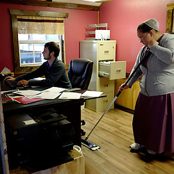 Melanie Mast , 17, wearing a traditional Mennonite dress cleans as owner Kris Zimmerman a fellow mennonite works at his desk at 5-Star Buildings in Cuba, Missouri on Tuesday, Sept. 27, 2016. (Photo by Keith Birmingham Photography)