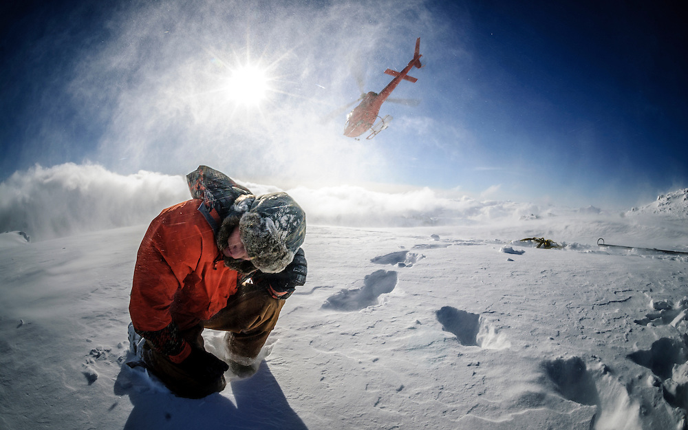 A helicopter drops off a worker on a remote mountain peak to install a radio repeater