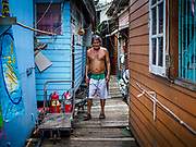 11 JULY 2017 - BANGKOK, THAILAND: A resident of a riverfront community walks through the community, one of many built over the Chao Phraya River south of Krung Thon Bridge. The residents of the community expect to be evicted and their homes destroyed to make way for the city's plan to build a 14 kilometer long (22 mile) riverfront promenade. Thousands of families are expected to be evicted to accommodate the promenade. The riverside communities, built on stilts over the water, are prone to flooding and the city has been trying to control them for years. The houses are the only affordable housing for available to some of the poorest people in Bangkok.      PHOTO BY JACK KURTZ