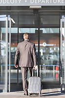 Businessman walking with his luggage in departure area at airport
