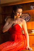 Young woman in an orange, strapless evening dress in front of an old dresser.